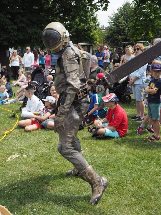 A man in a khaki astronaut outfit arrives into the crowd