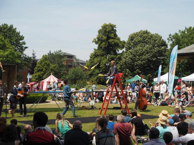 Two men juggling in front of a large crowd