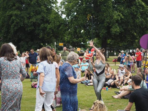 A lady in sequins leads people in a disco dancing session in the park