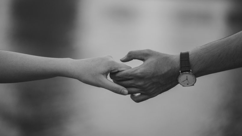 grayscale photo of holding hands