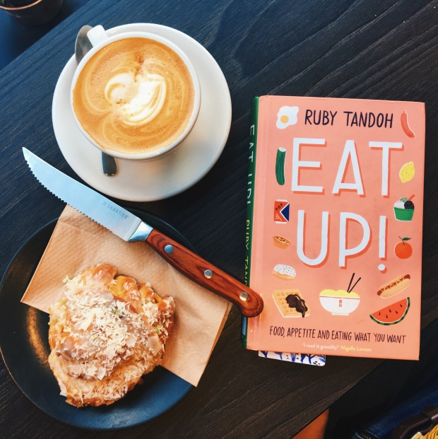 Ruby Tandoh's book, Eat Up, on a table with a coffee and an iced bun