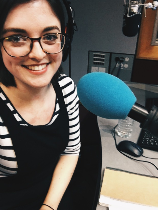 Jo Fisher taking a selfie at the radio microphone, smiling and wearing a stripy top