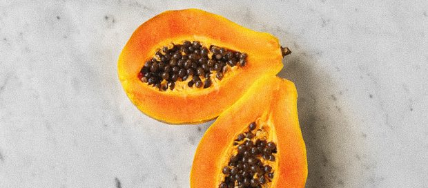 papaya, cut in half, on a marble surface