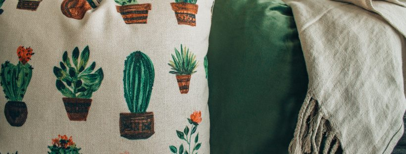 A cactus-patterned cushin and stone-coloured blanket draped on a deep-green, comfy looking sofa