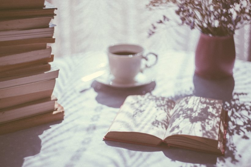 a sun-dappled table covered in a pile of books with a cup of tea