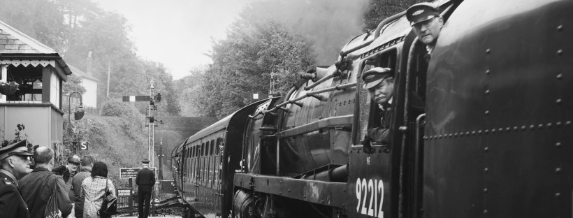 A steam train, with the crew leaning out, in black and white