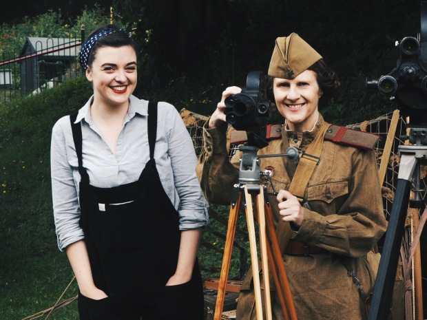 A girl in vintage dungarees next to a woman in WW2 soviet uniform with a video camera
