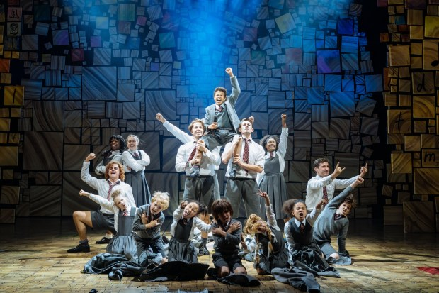 The children's cast of matilda pose on stage