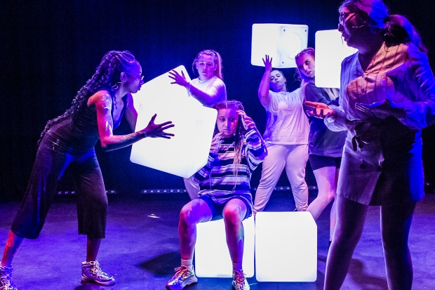 Young actors on stage playing with illuminated cubes