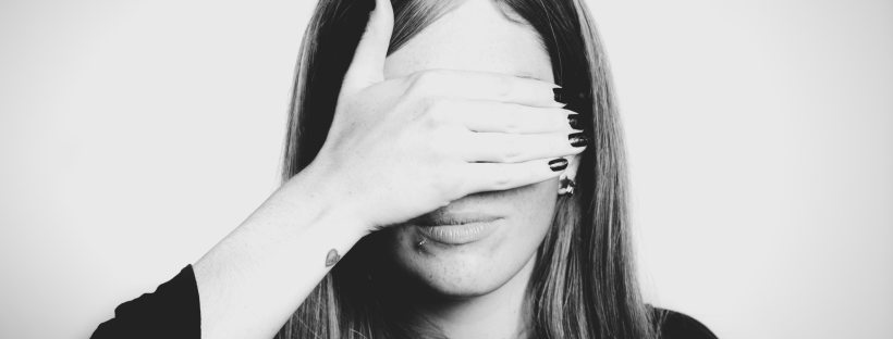 Black and white photo of a woman with long hair covering her eyes with her right hand