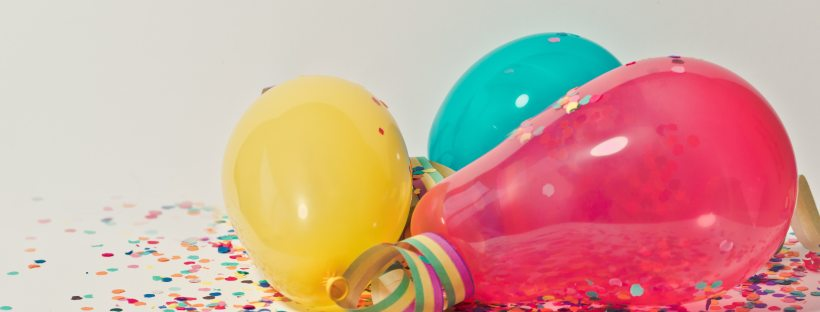 brightly coloured balloons with multicoloured confetti