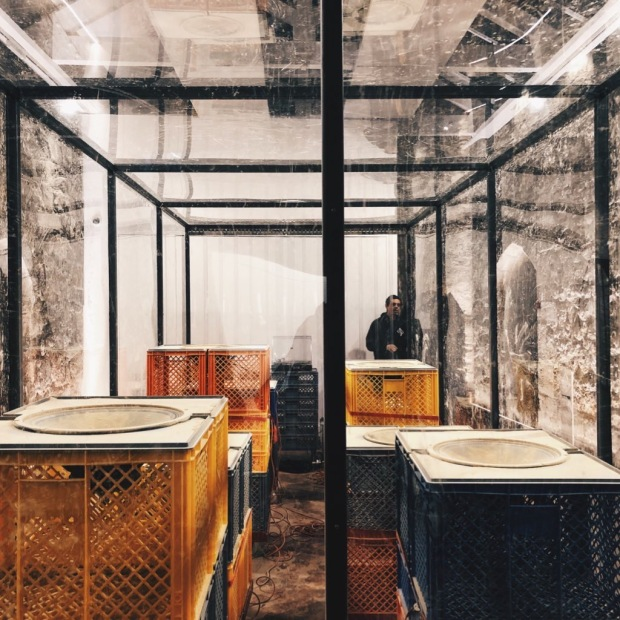 A transparent shipping container filled with upright speakers, with powder in them