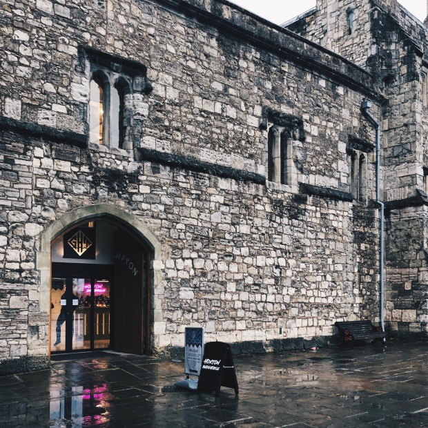 God's House Tower - an ancient wall - on a rainy day, with a neon sign shining through the door
