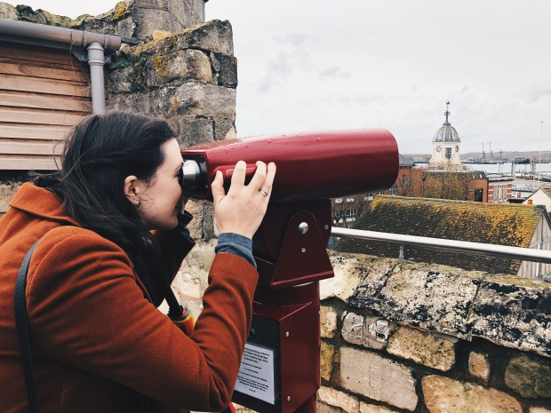A brunette woman looking through tourist binoculors from the roof of the tower