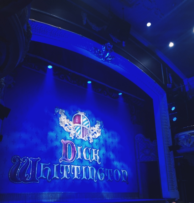 A theatre stage with the curtain down, with Dick Whittington on it