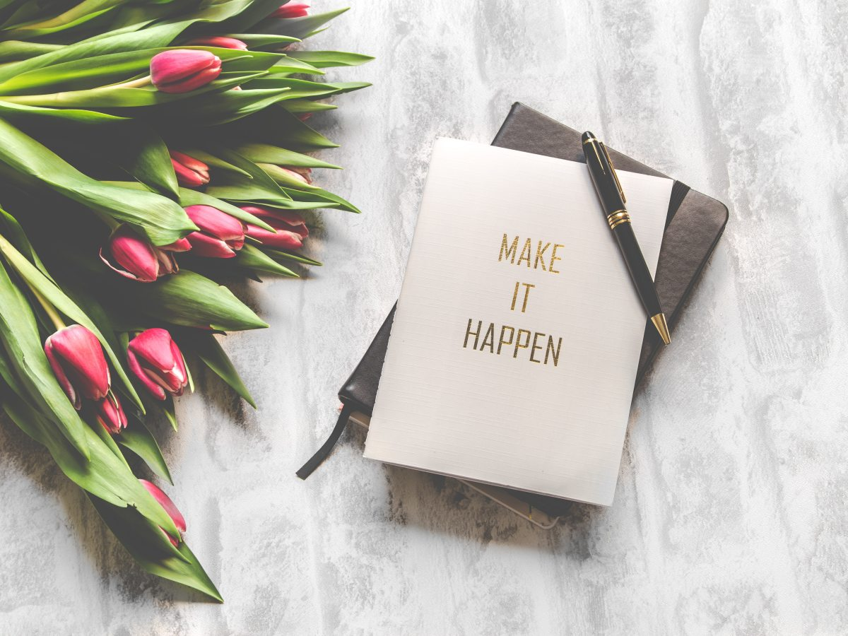 Tulips on a table next to a notebook with 'make it happen' on the cover