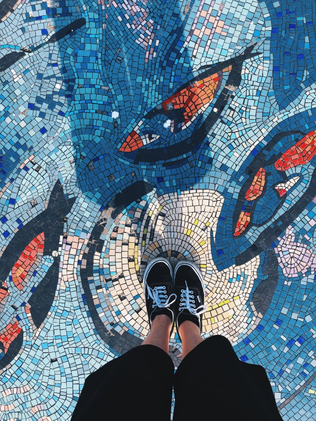 The camera looks down on a woman's legs, in trainers and culottes, standing on a mosaic of blue and orange tiles that look like fish swimming.