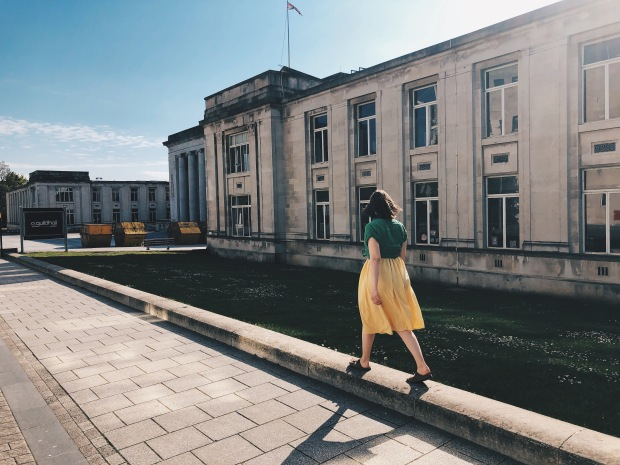 A girl with her back to the camera walks along a wall in a yellow long skirt and green shirt