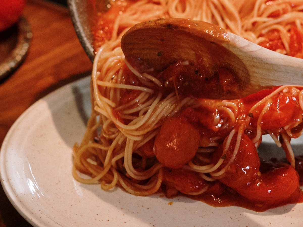wooden spoon tipping tomato pasta onto a plate from a pan