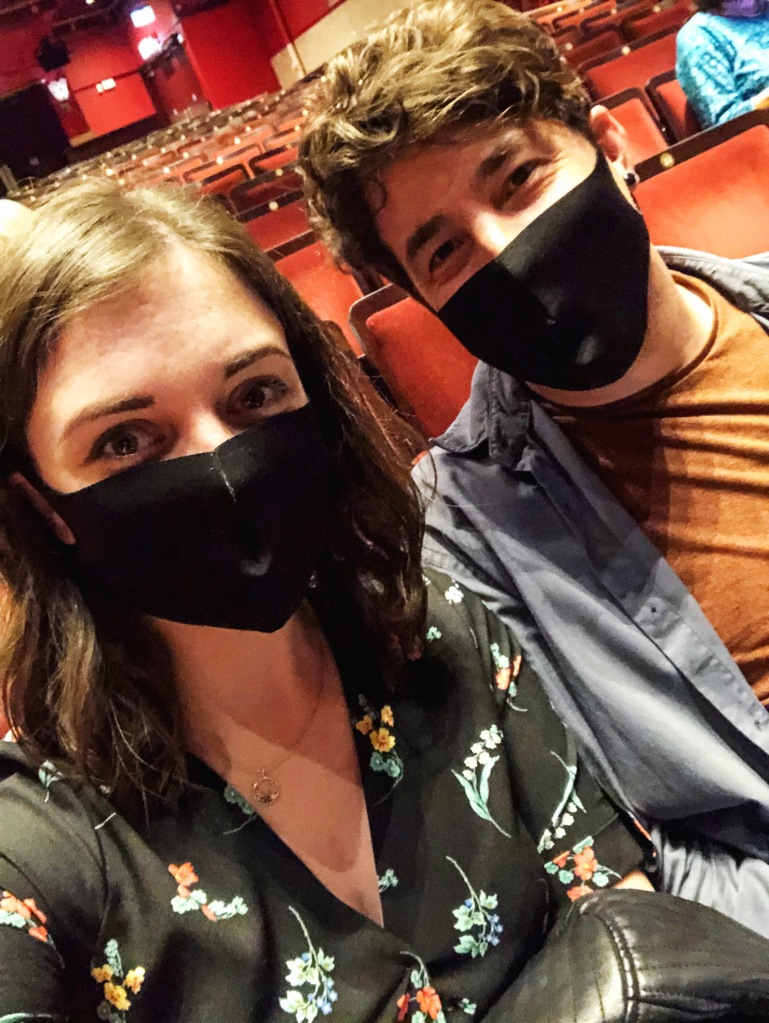 Two people taking a selfie with black face masks on, in a mostly empty theatre auditorium.