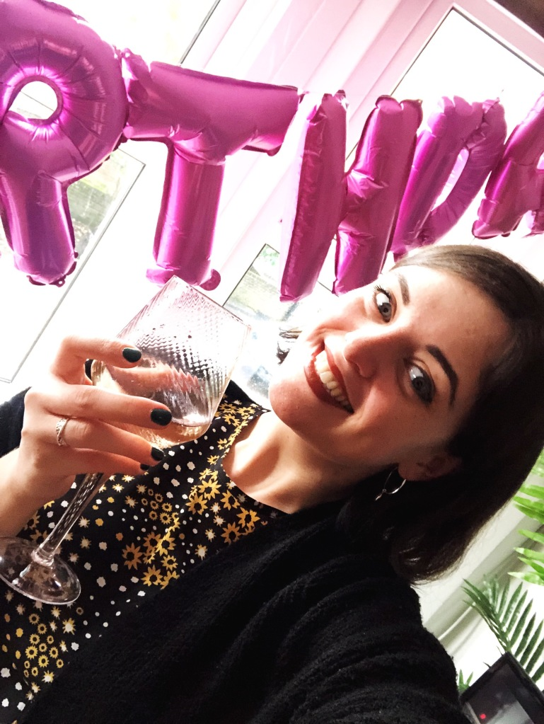 A brunette woman takes a selfie with red lipstick and a black and yellow flowered dress; she is topping her head and holding a glass of wine in one hand; in the background, you can see pink balloons partially spelling out 'Happy Birthday'