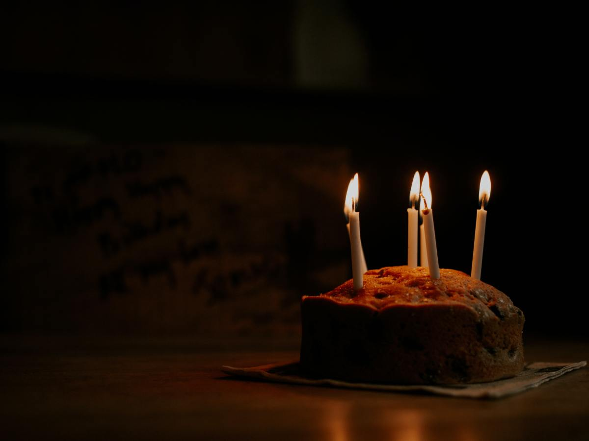 A simple birthday cake with five candles in the dark, on a table.