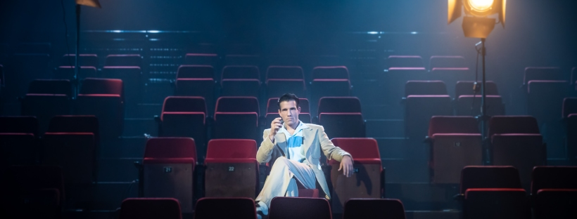 a man in a light-coloured suit lounges in a theatre seat