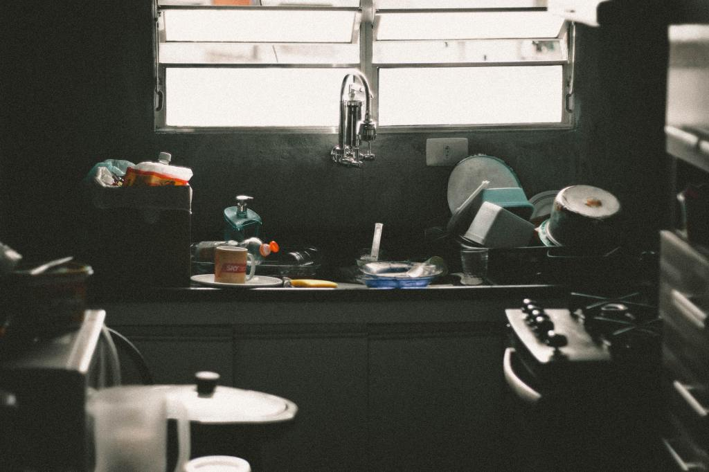 A messy kitchen in low-light