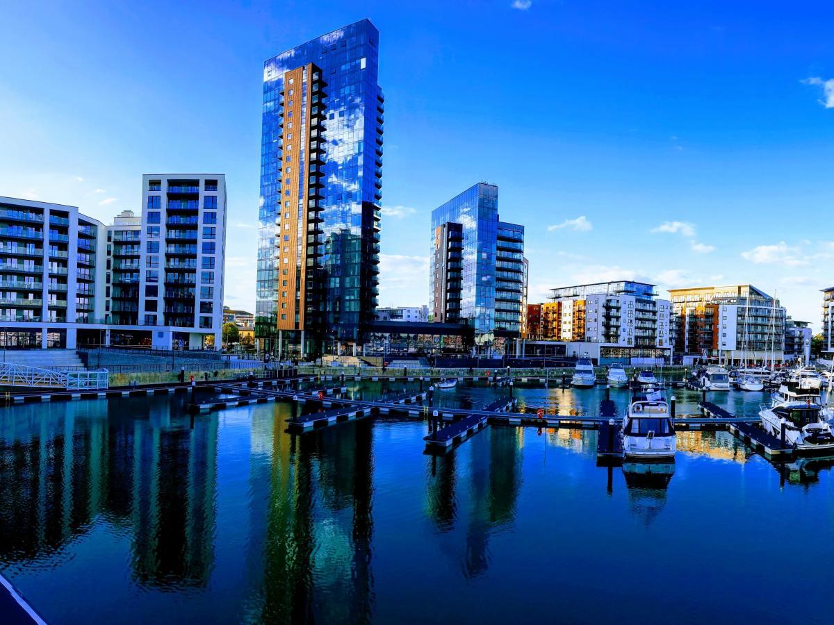 modern, tall flats next to a marina with bright blue skies