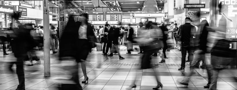 A grayscale, blurry photo of people rushing at a station in Japan