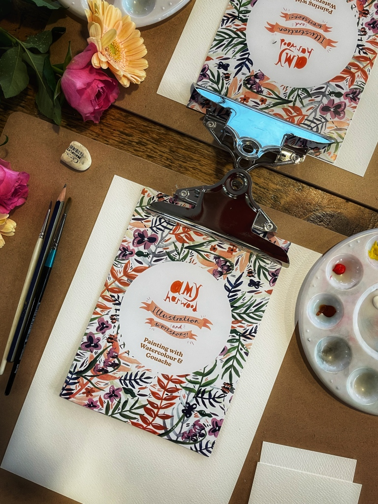 A flatlay image of a clip board with a paint palette, pencil, rubber and a  pamphlet with 'Amy Harwood illustration and workshops