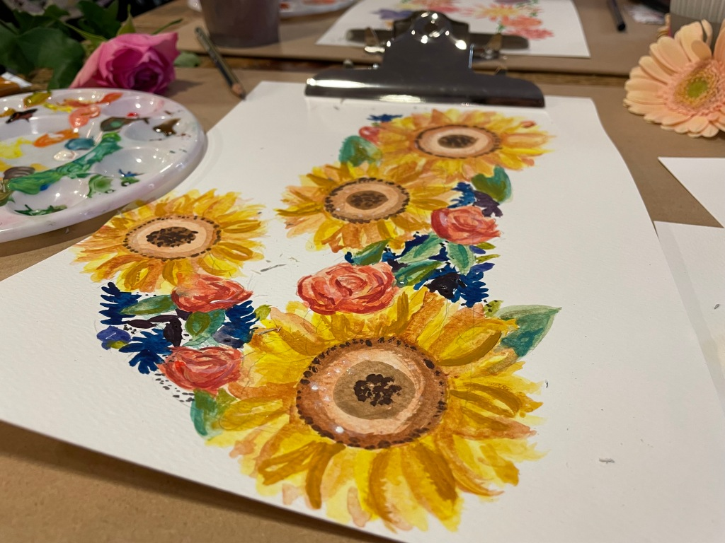 A painted 'J' made of watercolour sunflowers and roses, photographed at an angle so you can see the messy paint palette beside it.