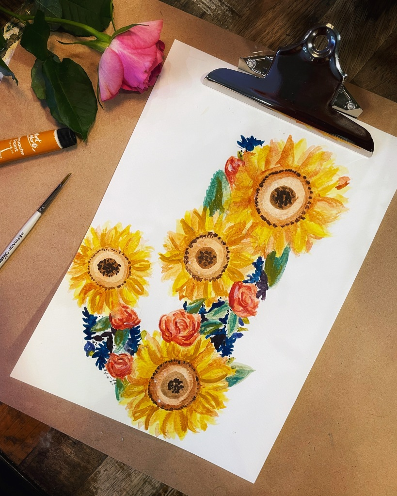 A 'J' made of hand painted sunflowers, peach roses, green leaves and blue shapes; a pink rose and a paint tube peeps from the side.