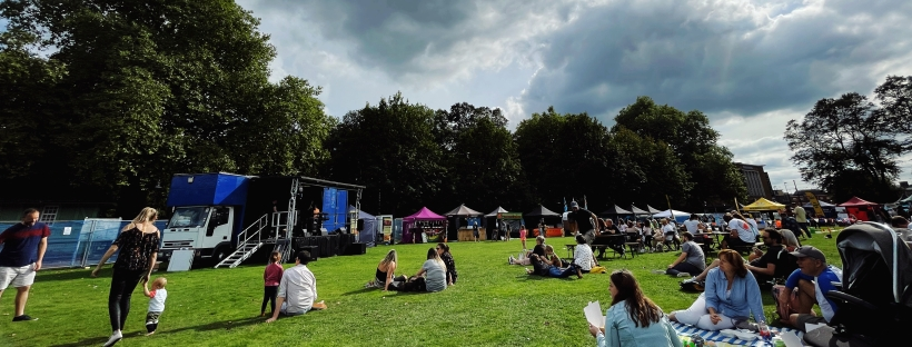 People sitting on a field surrounded by festival stalls, watching a stage