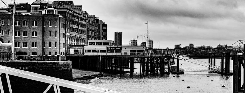 A black and white photo of London's south bank, with part of the river and a couple of industrial looking docks