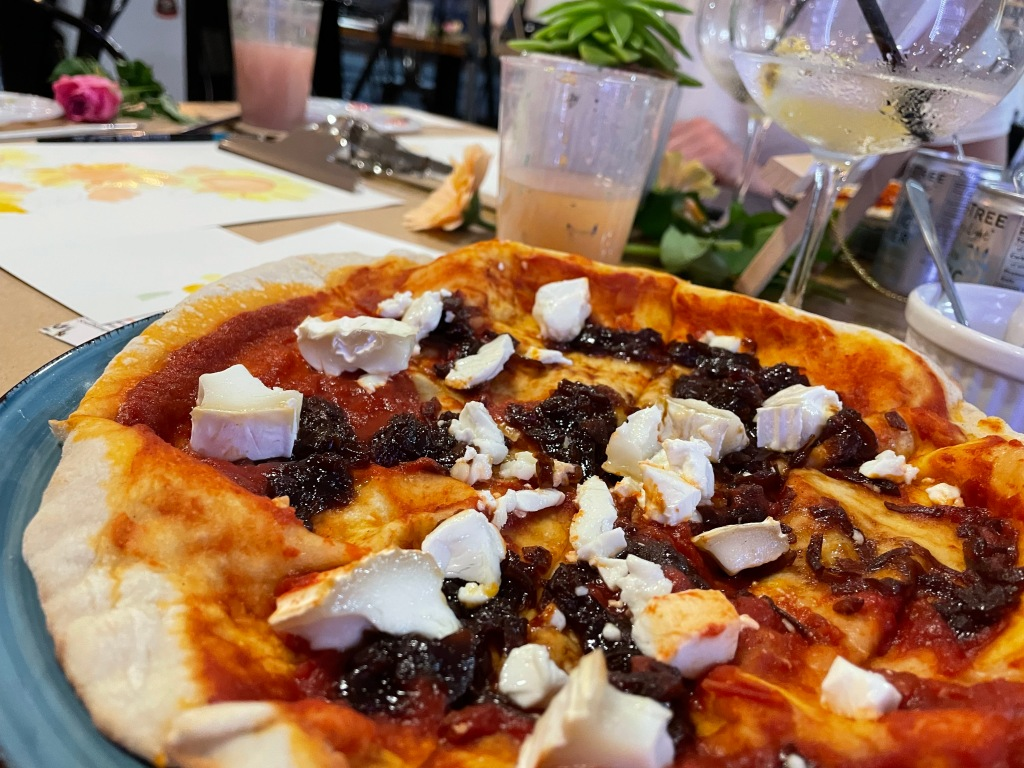 A goat's cheese and onion marmalade pizza; behind it, you can see a glass of paint-filled water, a gin and tonic, and a blurred painting