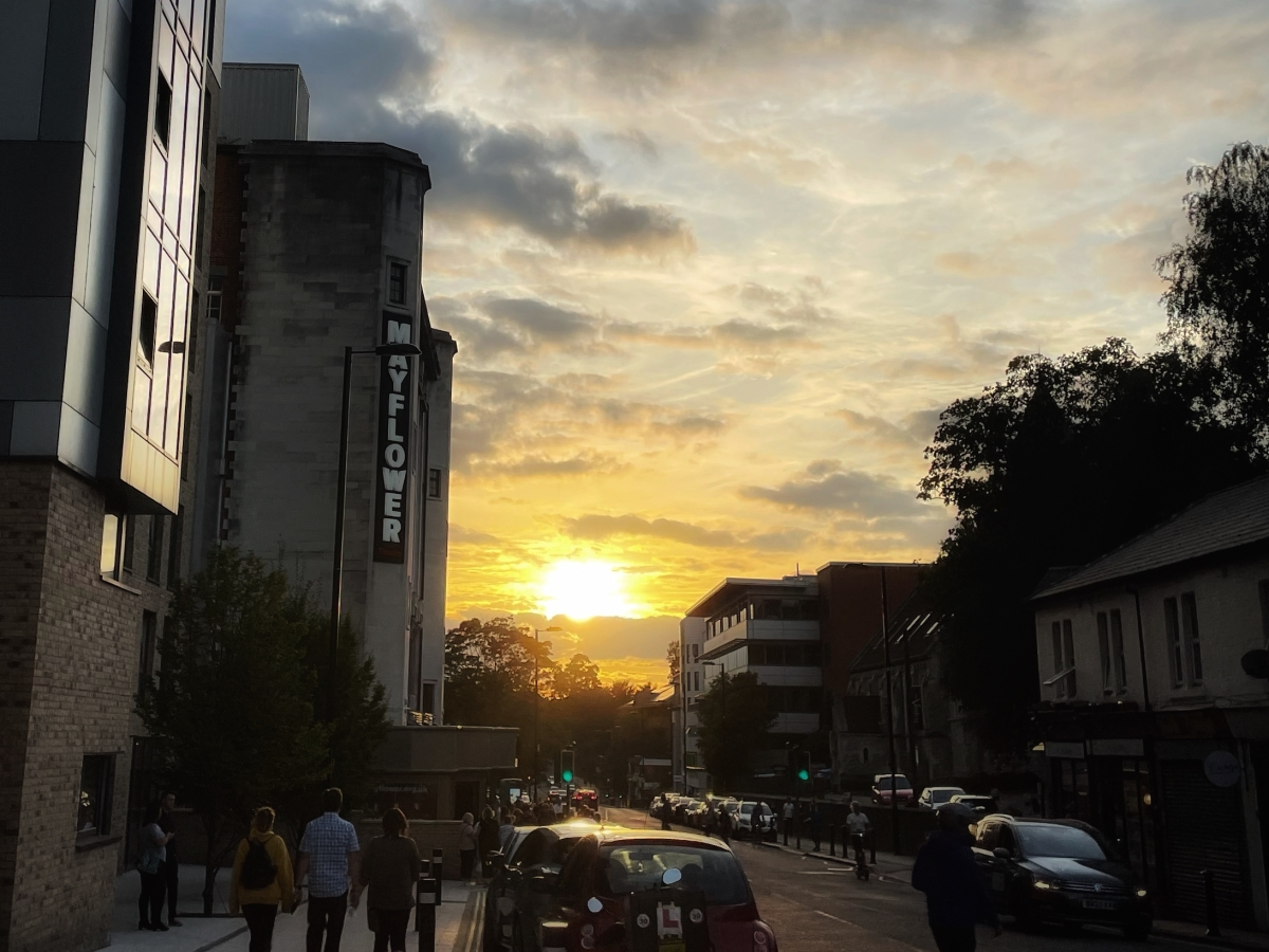 A sunset behind a building, with a sign saying Mayflower Theatre